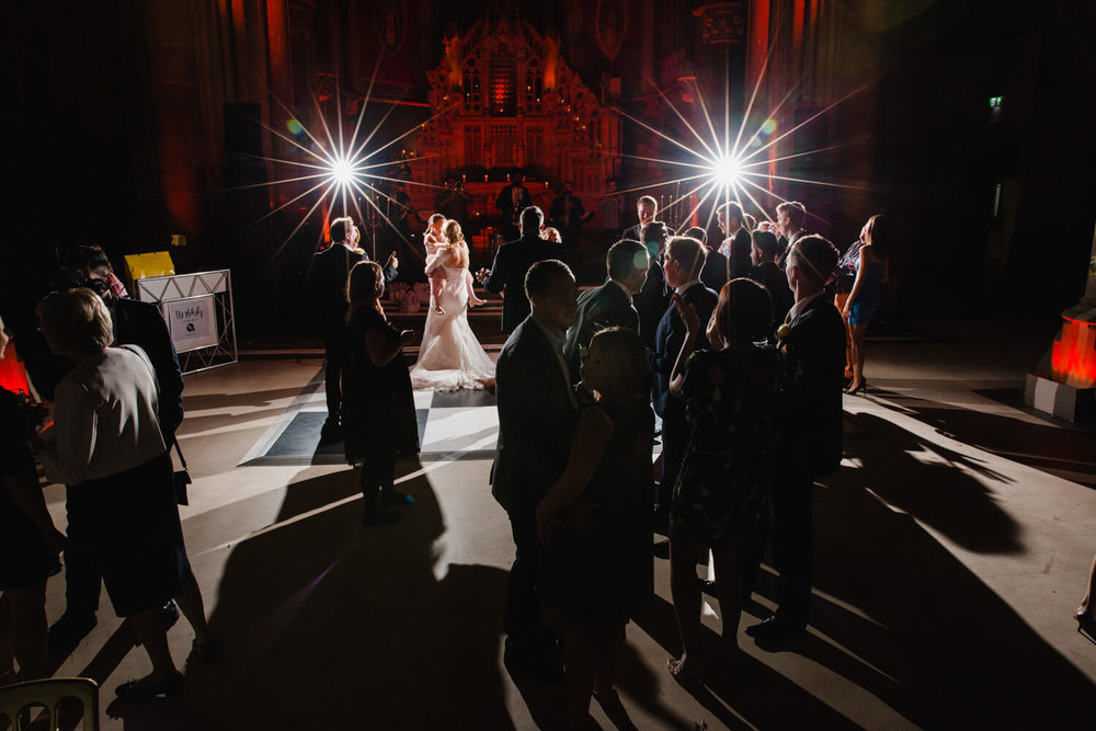wide angle photograph of dance floor full of friends and family dancing bride lit up by aperture flash starbursts