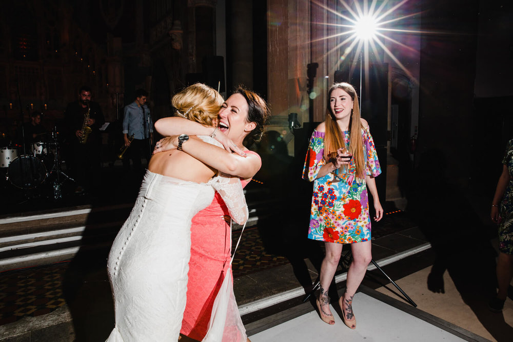 bride hugging wedding guest who celebrates with party