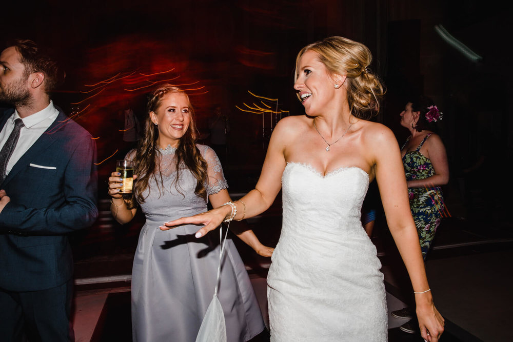 bride and bridesmaid dancing together on dance floor
