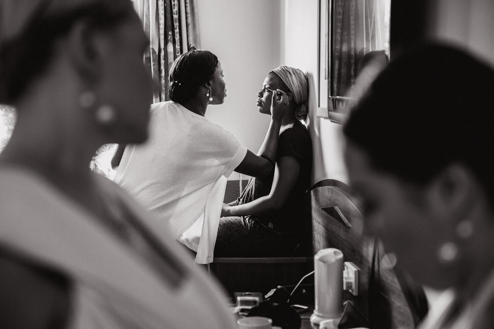 black and white photograph of bride having make up by wall of hotel