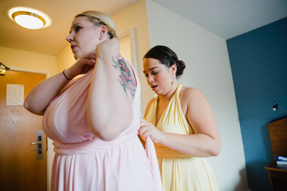 bridesmaids fastening up dresses in bridal suite