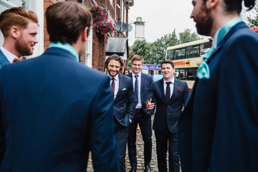 wedding guests make their way from the pub to the ceremony
