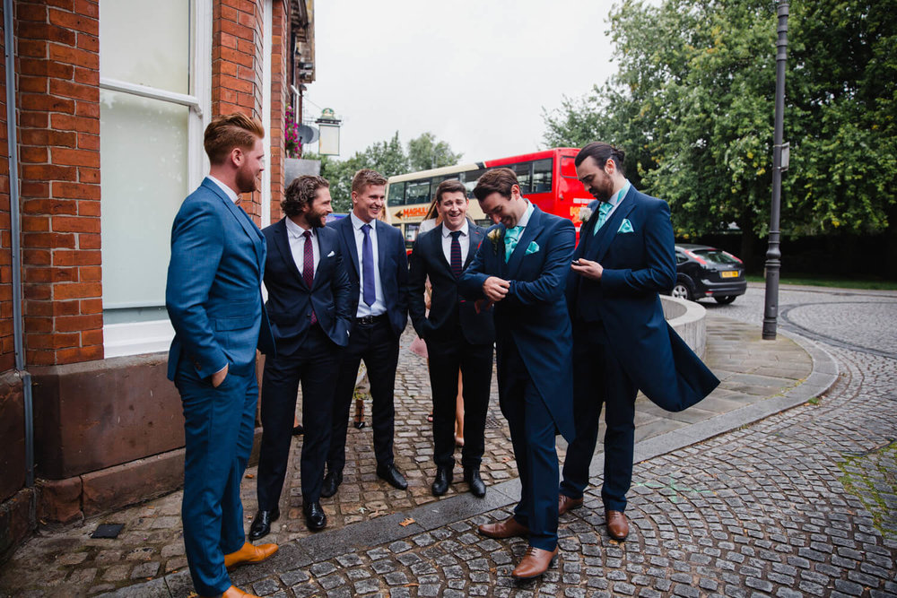 groomsmen grouping up outside pub before the wedding