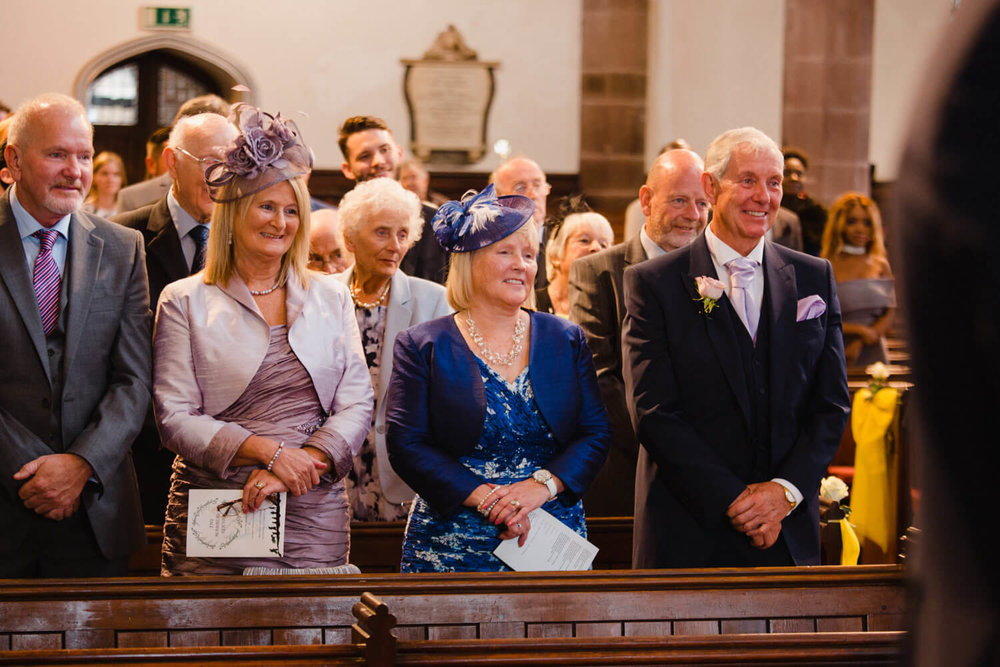 wedding guests sat at the top of aisle watching bride and groom exchange vows