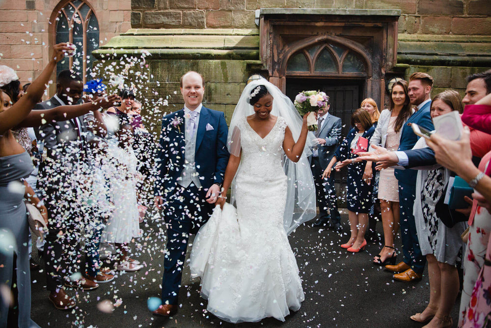 newly wedded couple walking through confetti thrown by family and friends