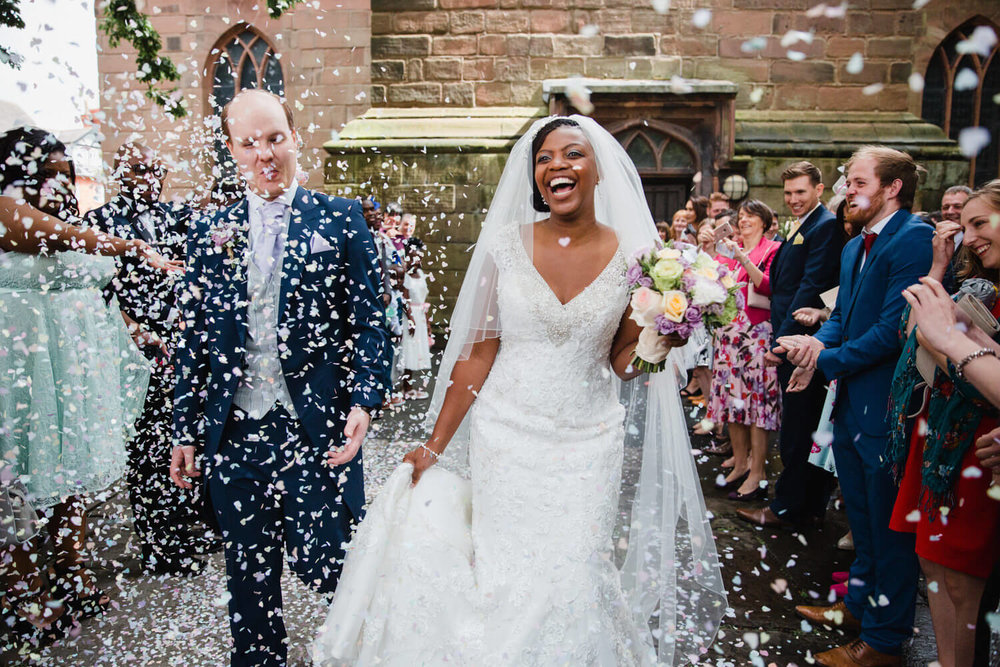 close up of bride and groom walking through confetti outside church