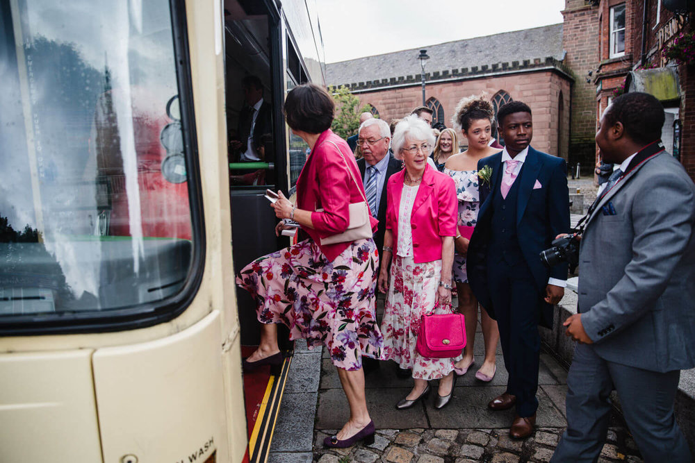 wedding guests boarding double decker bus taking them to reception venue