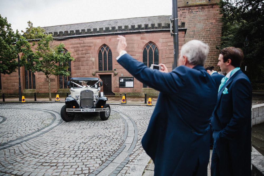 father of groom waving to bride and groom in wedding car