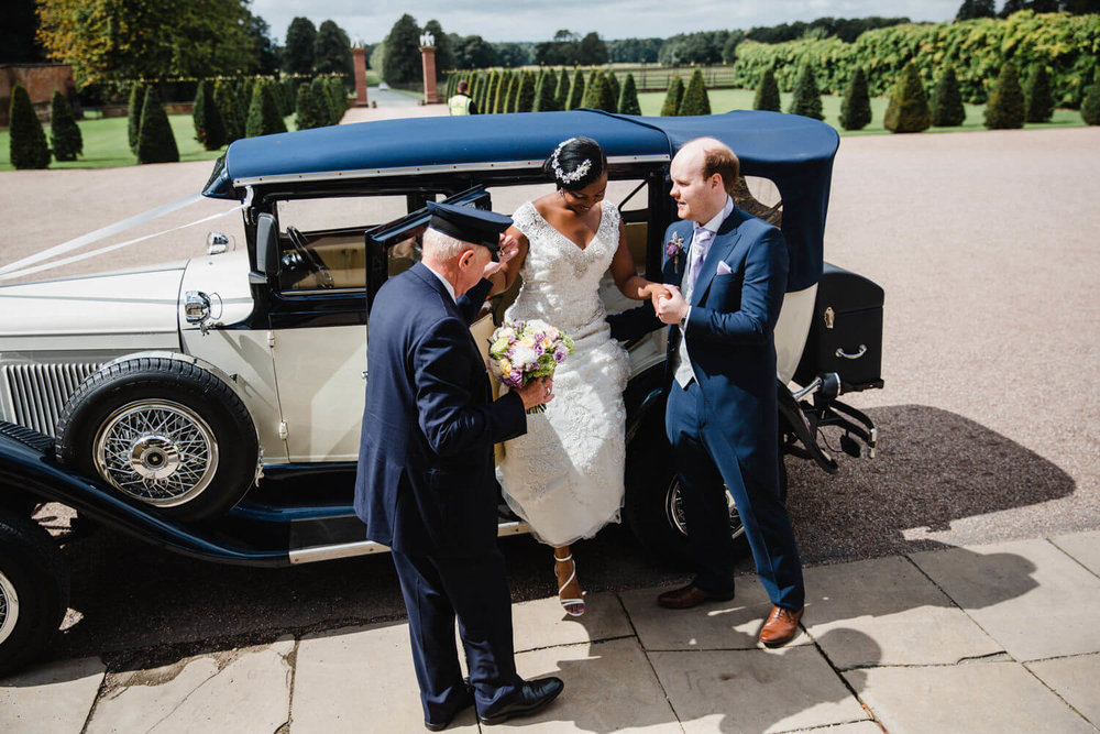 bride getting out of wedding car assisted by groom and chauffeur