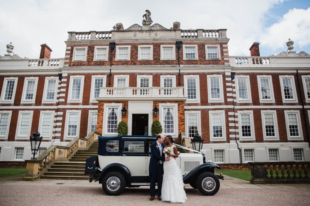 newlyweds in stood in front of wedding car and knowsley hall wedding venue