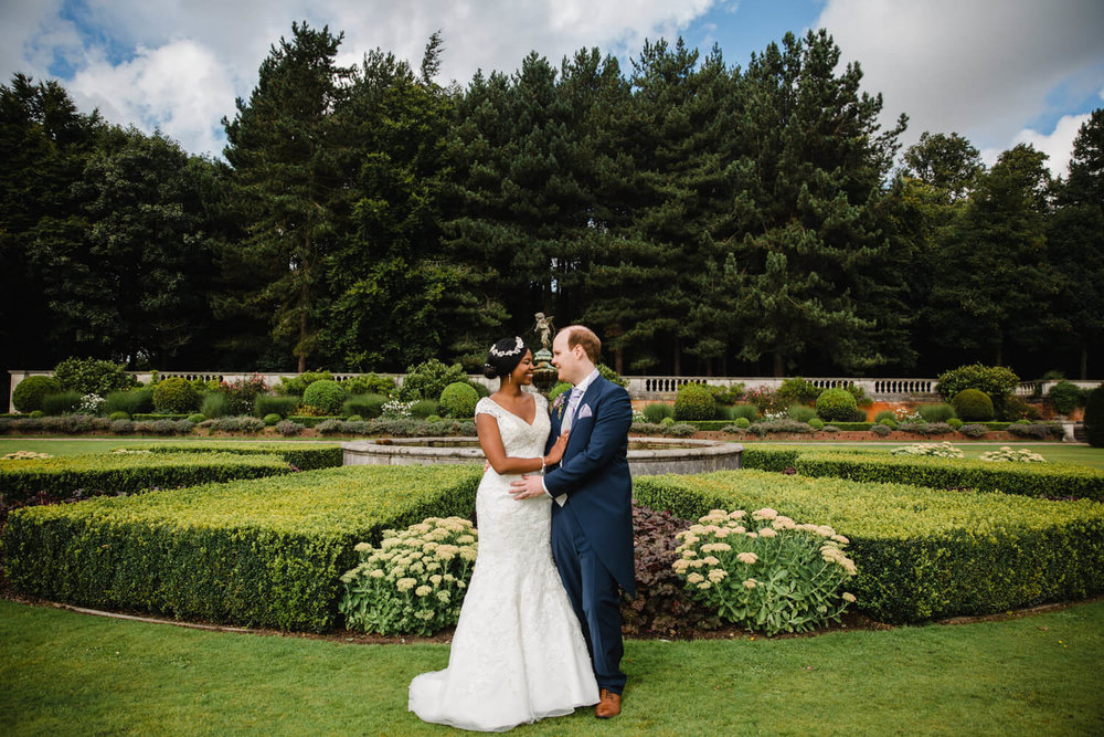wide angle portrait of newlyweds in front of fountain at knowsley hall