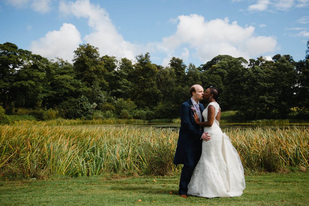 portrait of bride and groom sharing intimate moment kiss in front of lake at knowsley hall