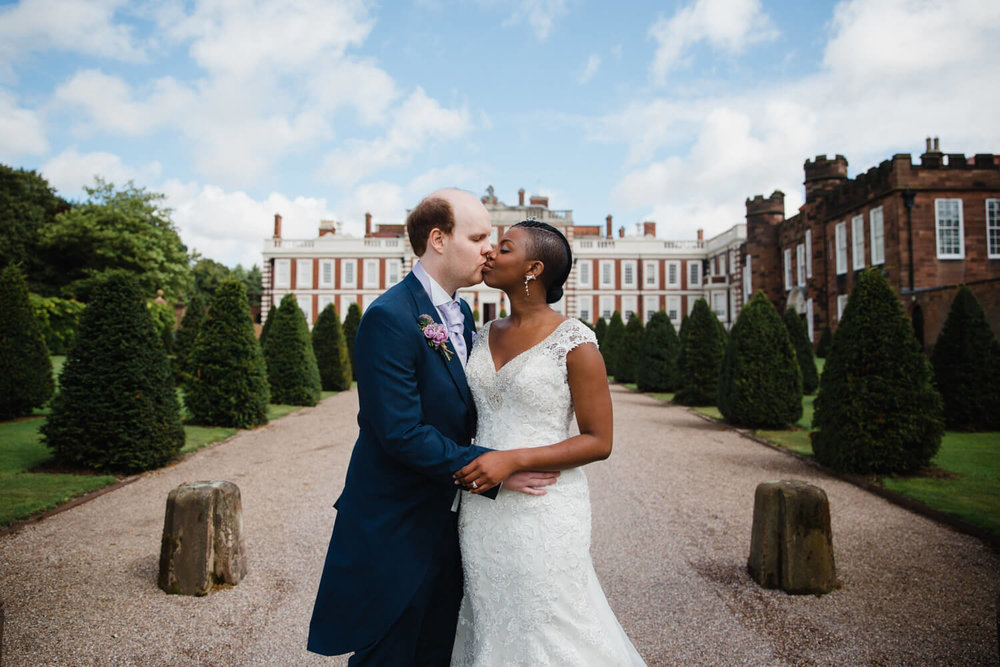 bride and groom kissing in front of knowsley hall wedding venue
