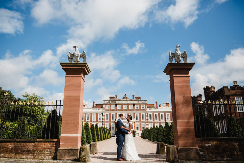 wide angle photograph of bride and groom holding one another in front of knowsley hall wedding venue