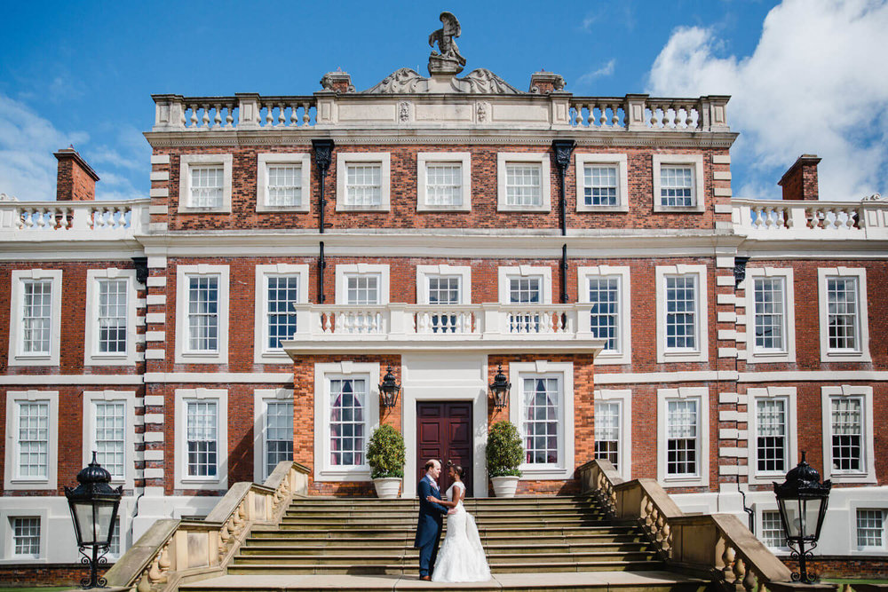 wide angle photograph of bride and groom in front of knowsley hall