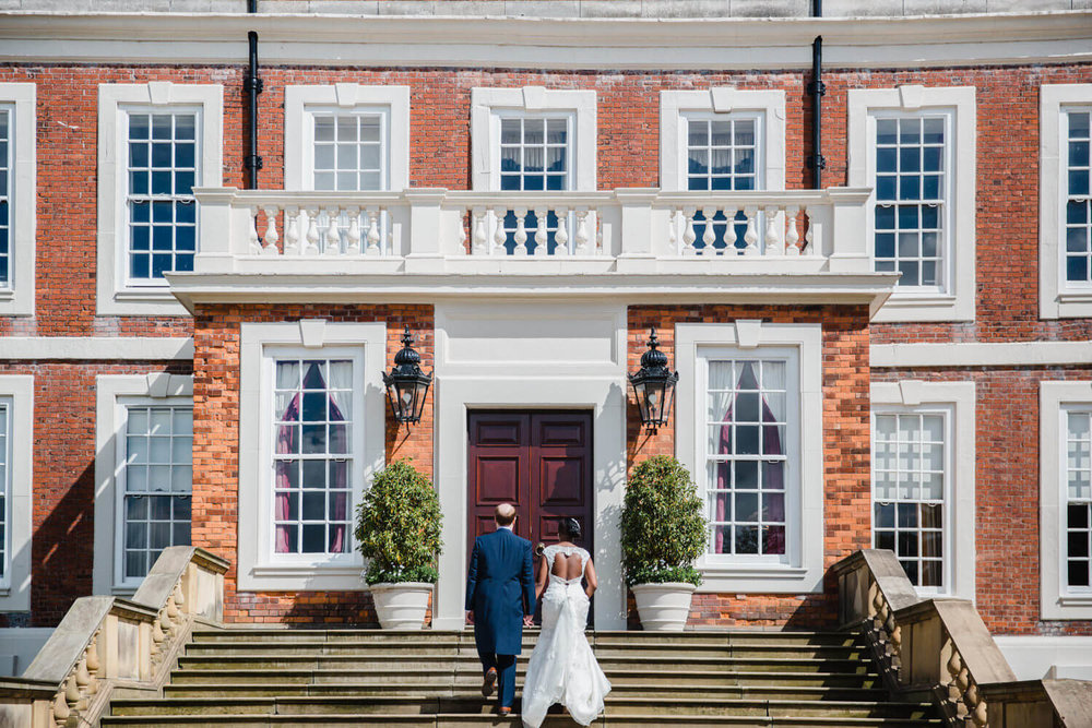newly wedded couple walking up steps to knowsley hall entrance