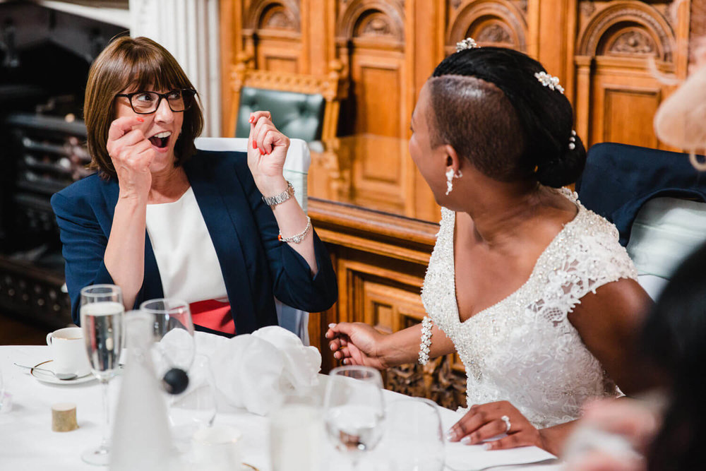 wedding guest laughing with bride sat at table