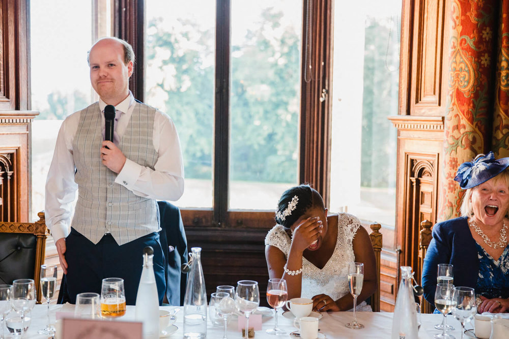 bride laughing with head in hands with groom giving his speech to wedding party