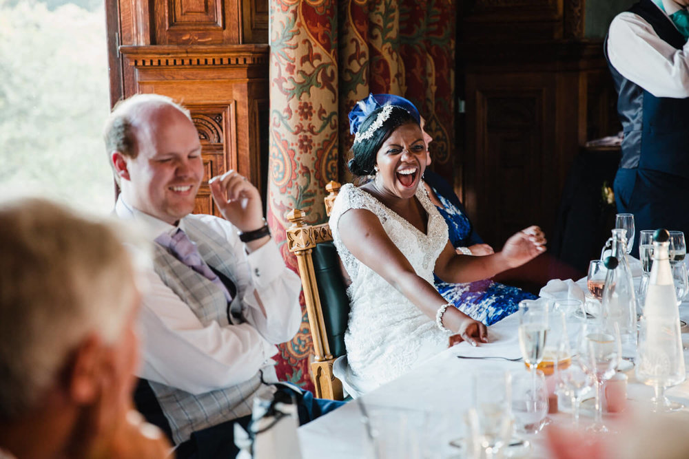 bride laughing out loud at wedding guest speech