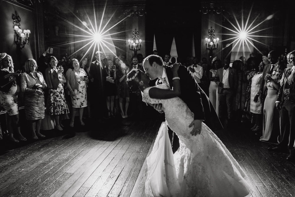 groom dipping bride surrounded by family and friends during first dance at knowsley hall
