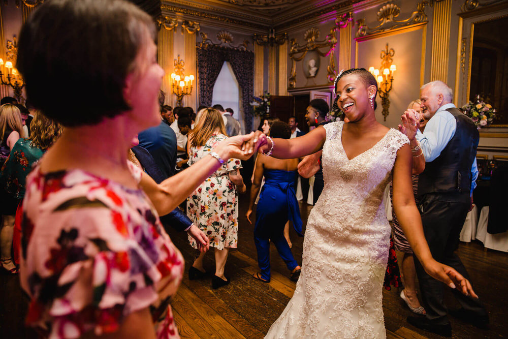 bride dancing with friend to DJ music at wedding party