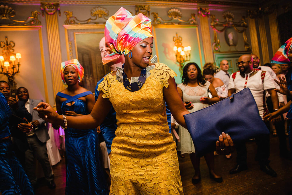 bride in traditional african clothing dancing with guests at knowsley hall