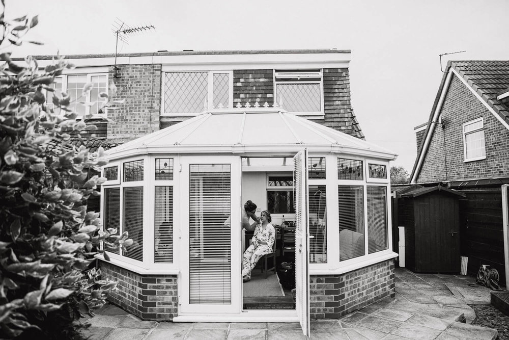 black and white of conservatory from garden with bride having make-up