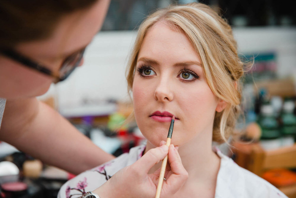 bride having lipstick pencilled on by make-up artist