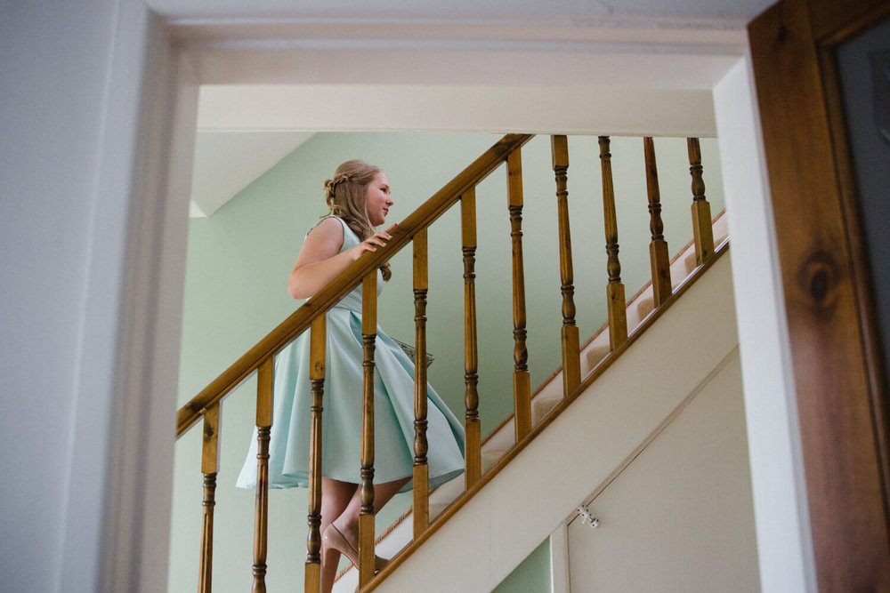 bridesmaid climbing up stairs in hallway