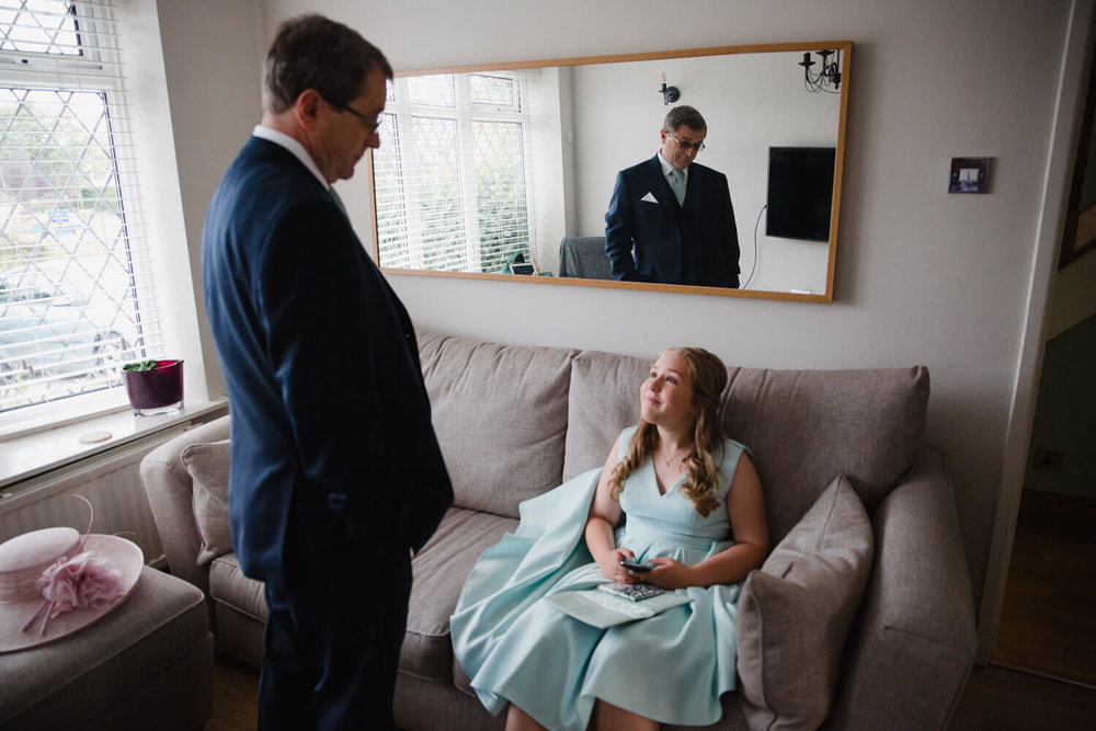 father of bride talking to bridesmaid with mirror reflection on living room wall
