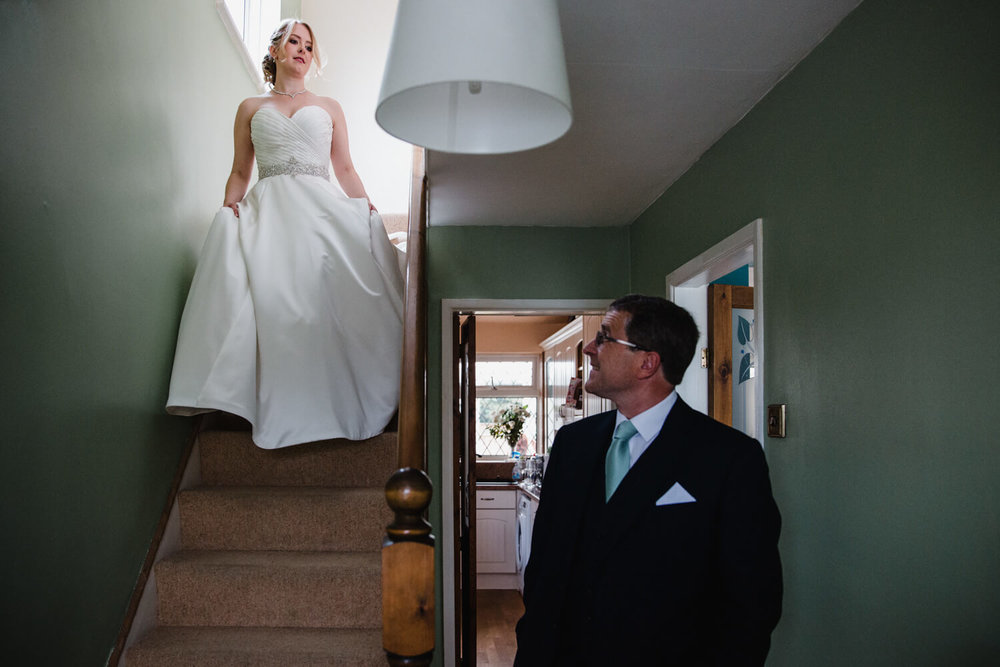 bride walking down stairs in wedding dress with father first look at bottom