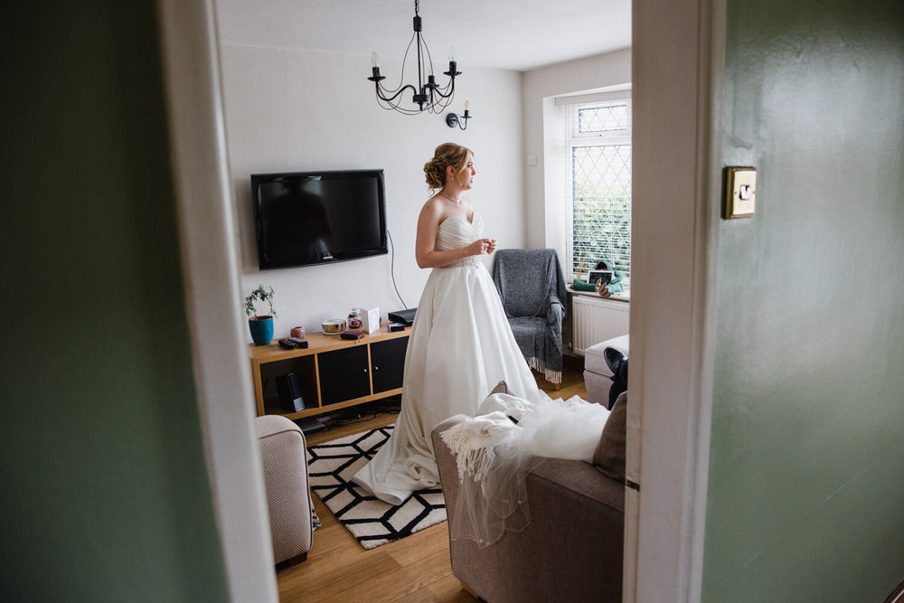bride waiting in living room looking out of window for car to arrive
