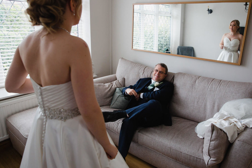 father and bride in living room with bride reflection in mirror