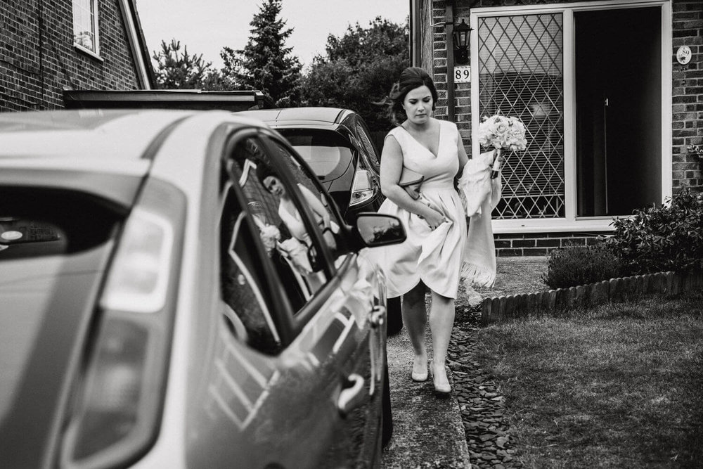 bridesmaid carrying bouquet out to car