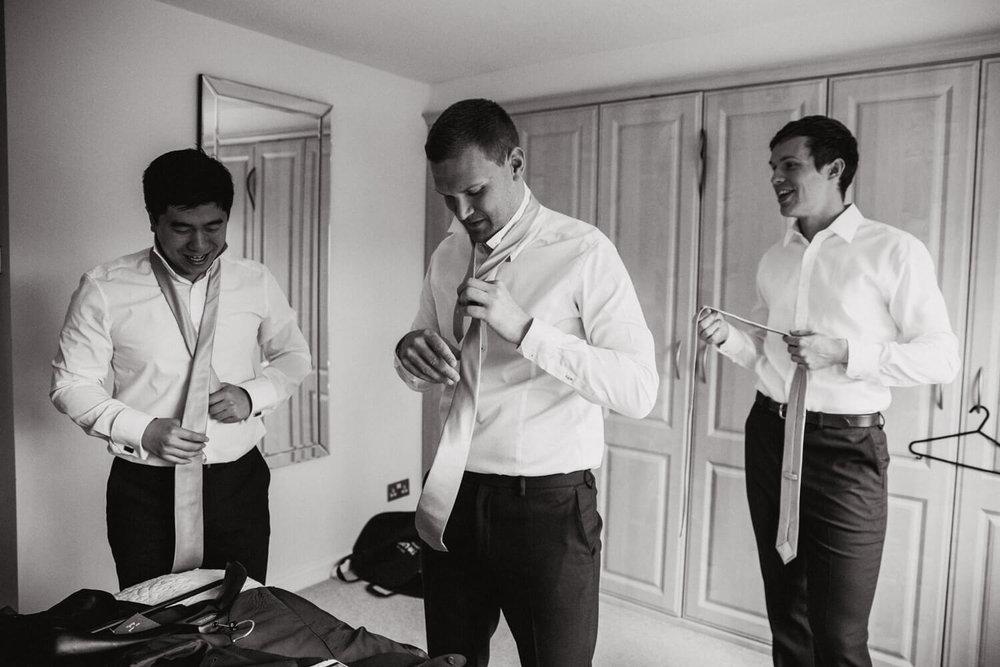 groomsmen fastening ties in bedroom