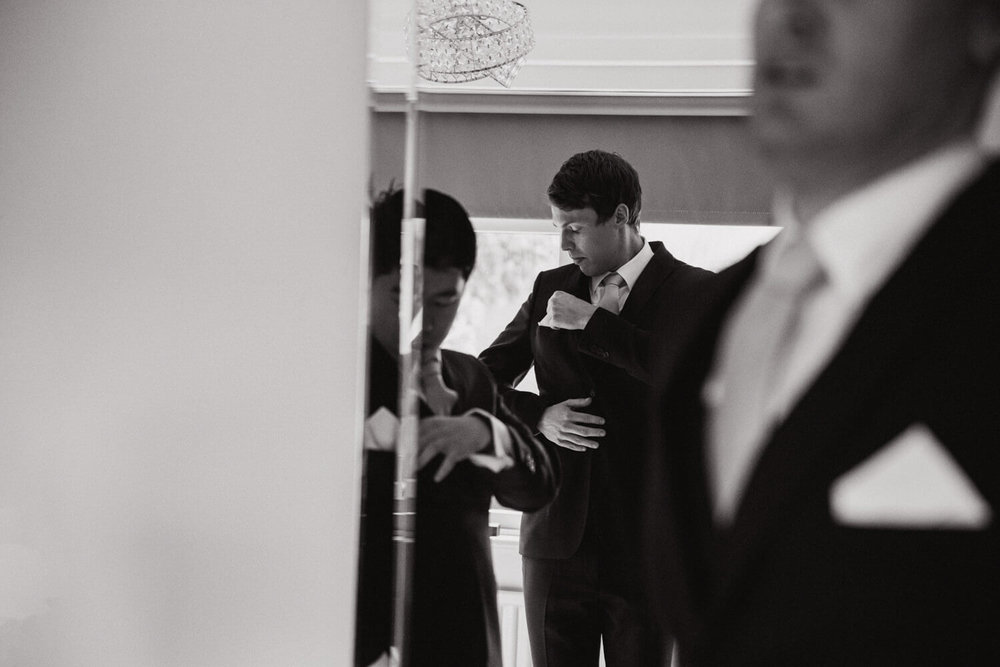 groom fixing pin-hole flower to lapel of suit jacket in mirror