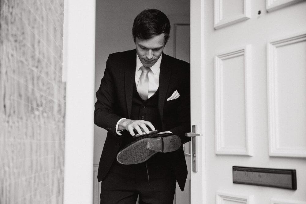 groom polishing his black shoes in doorway before wedding