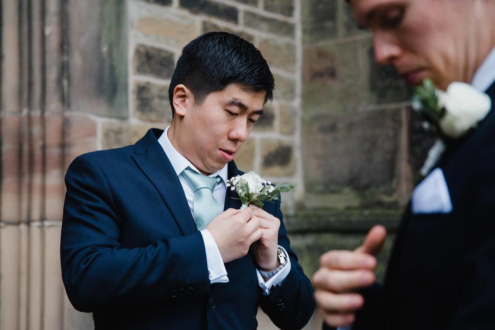 usher pinning flower to jacket pocket of suit