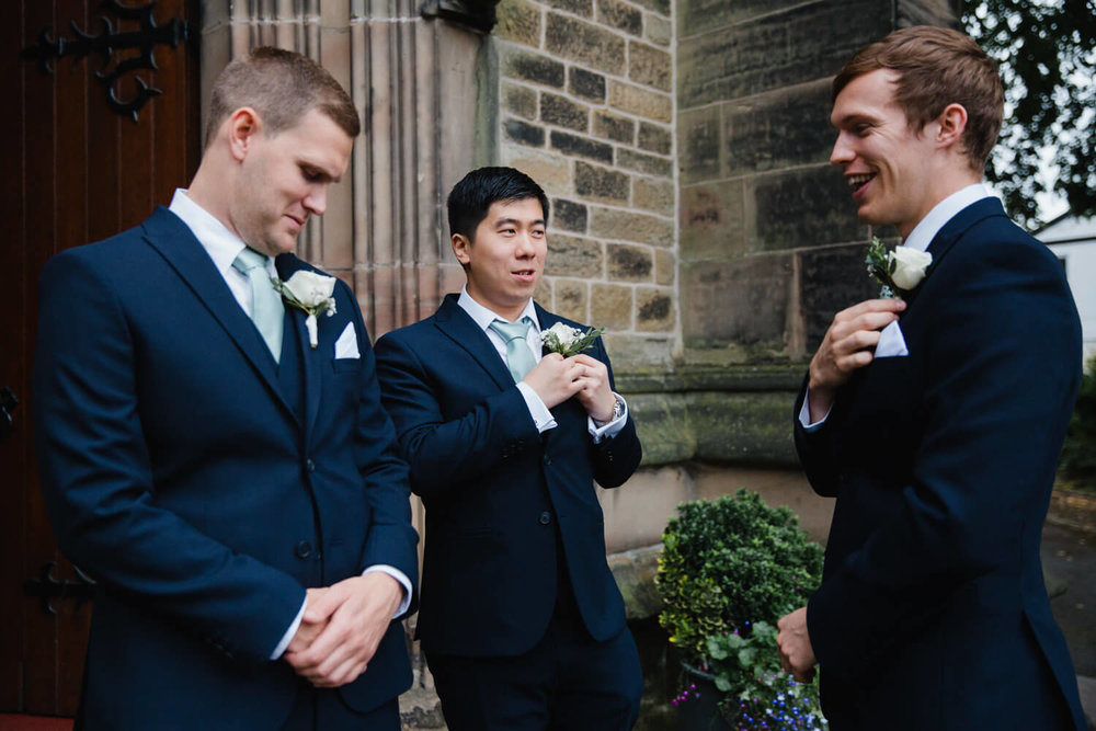 groomsmen at front of church preparing for ceremony