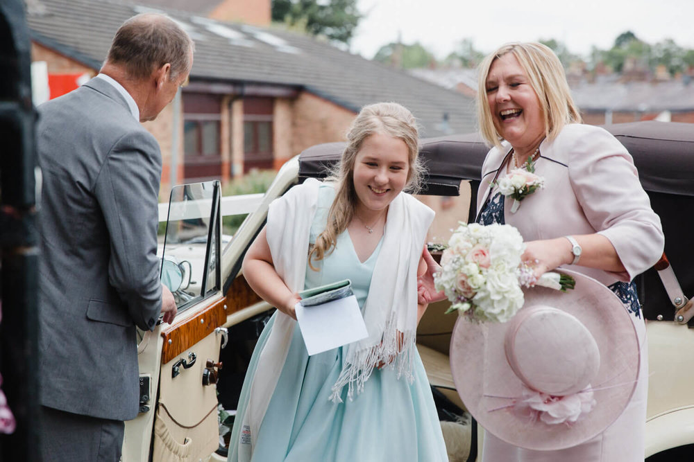 bridesmaid and mother walking past chauffeur driver to church