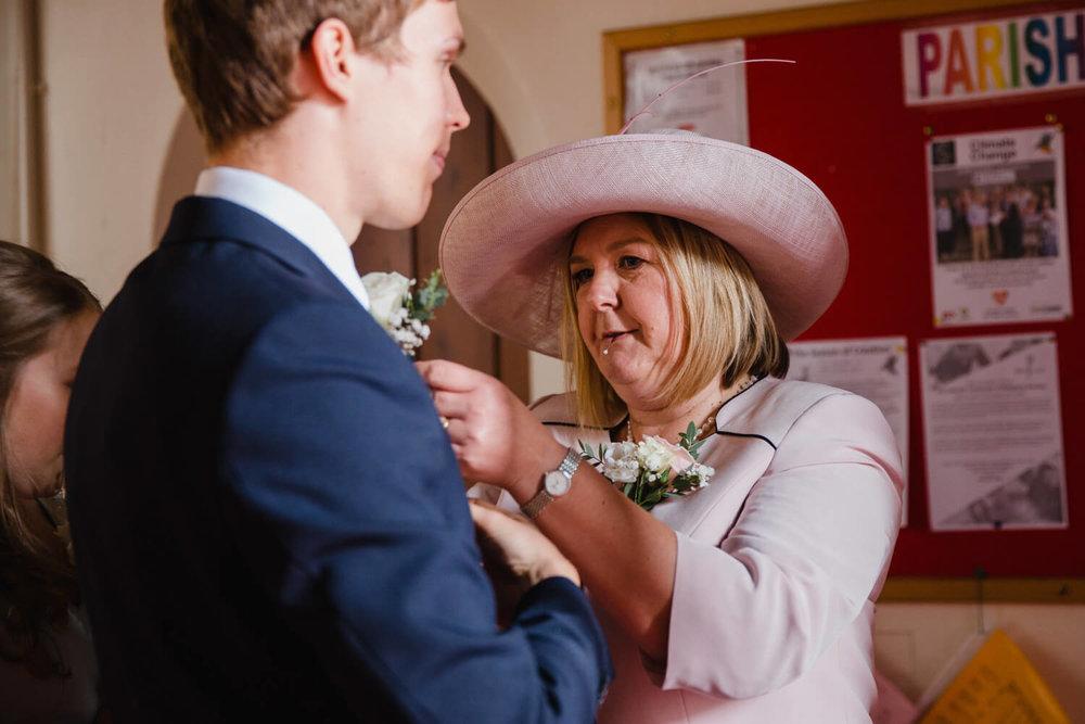 mother of bride fastening flower to groom jacket