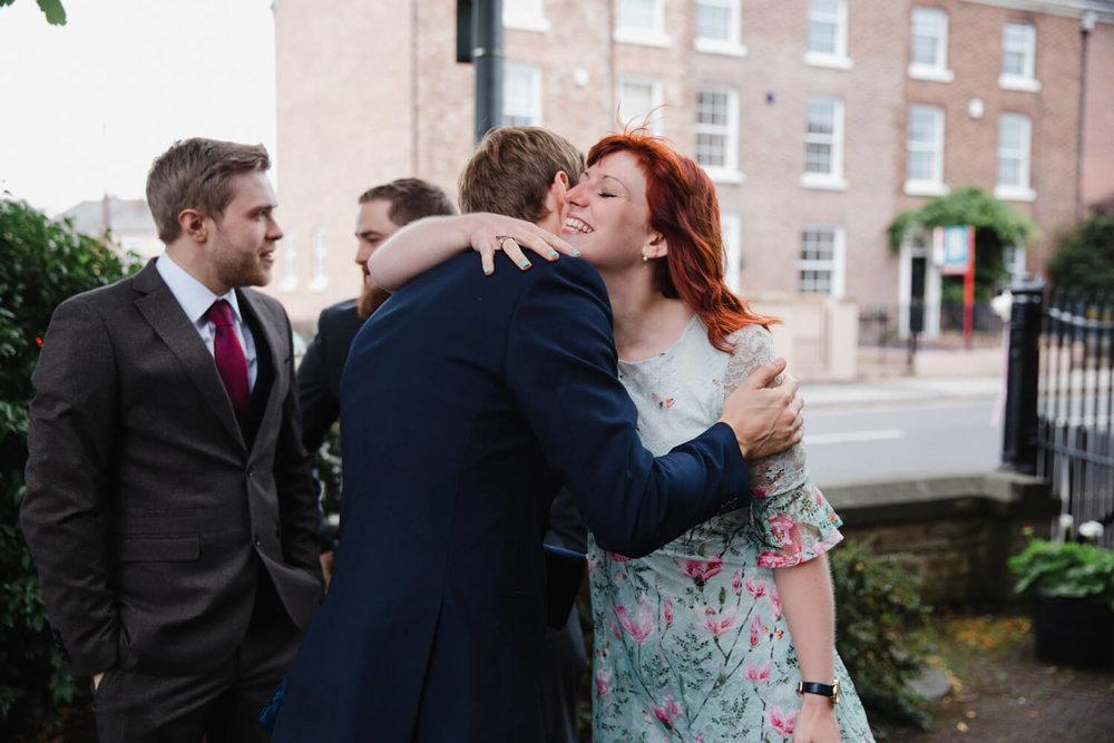 bridesmaid enjoying hug with wedding guest