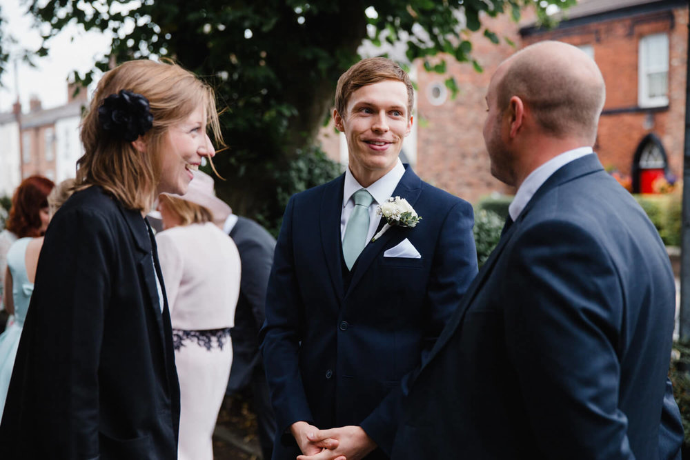 groom chatting with parents outside of church