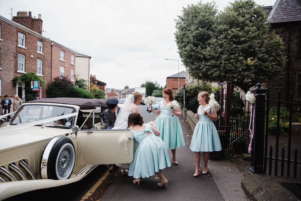 wedding car arrives, bridesmaids holding bouquets while helping bride to church