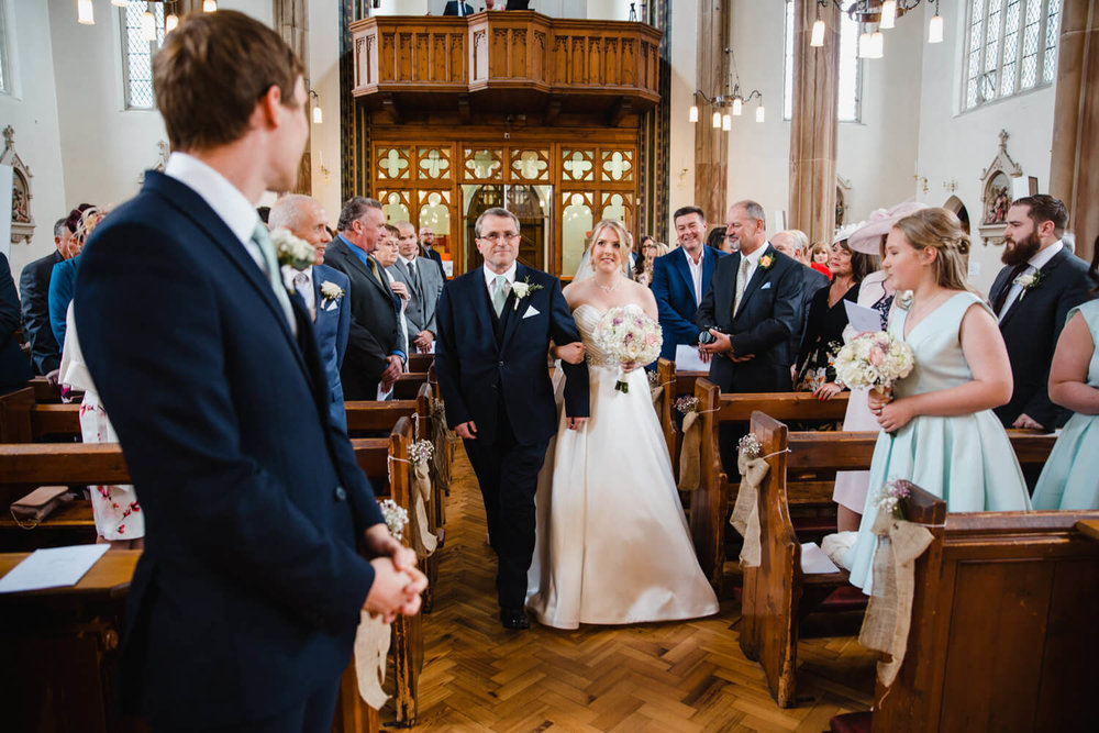 bride halfway down aisle linking arms with father with wedding guests and families looking on
