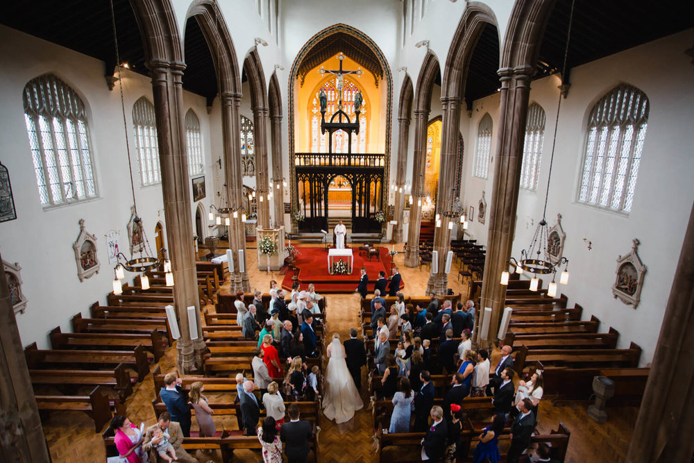 wide angle photograph from the back of church service with bride and father walking down aisle and all family and friends watching the beginning of ceremony