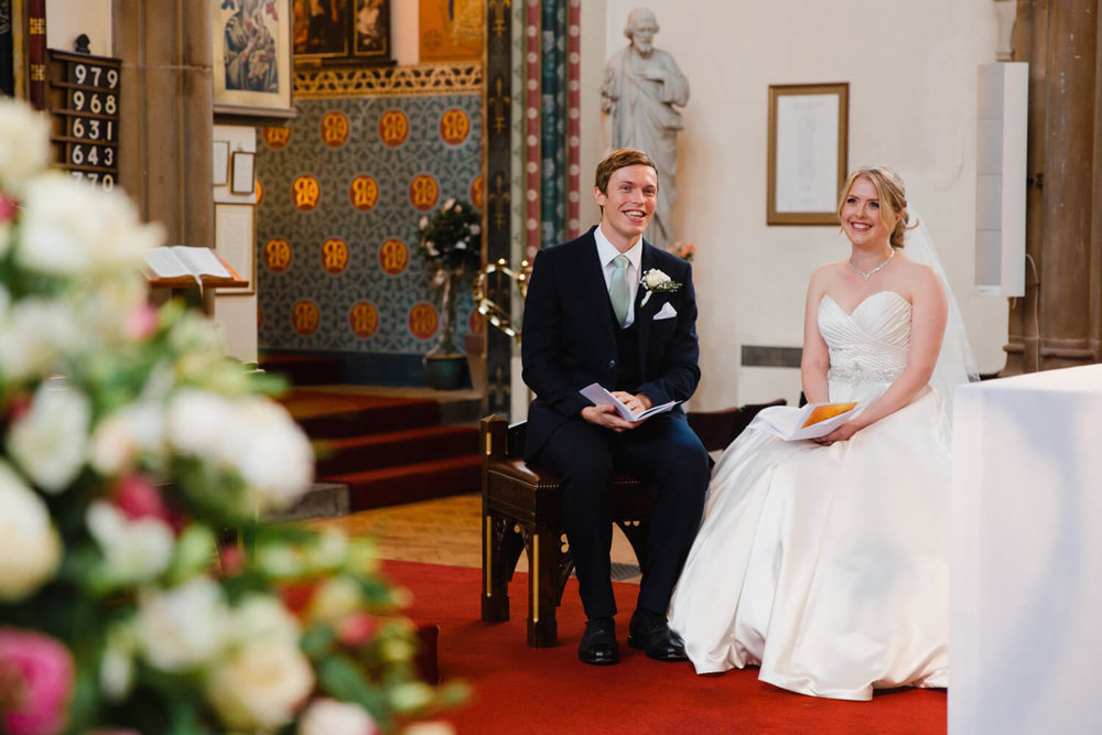 bride and groom sat together at front of service looking at priest