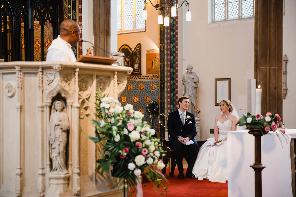 bride and groom laughing together on alter of church during service