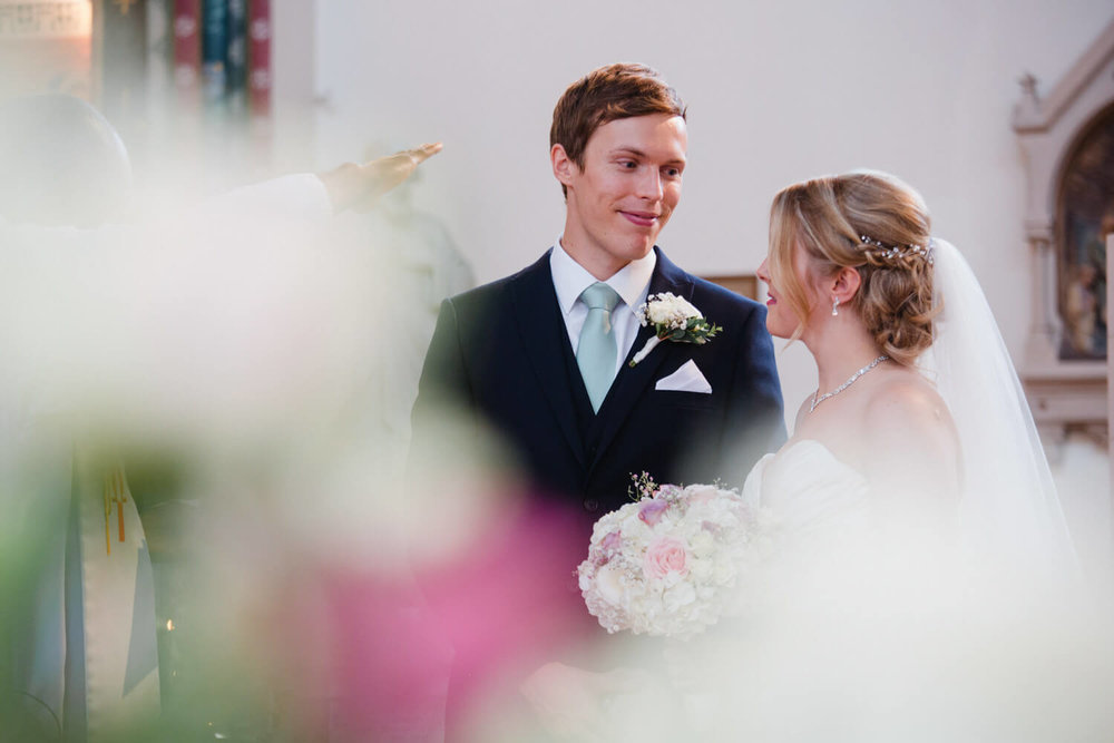 bride and groom exchanging wedding vows during service with bouquet blurred in foreground of photograph