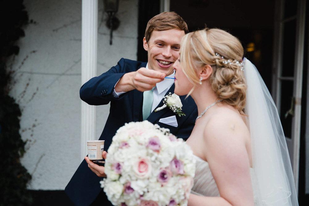 groom feeds bride ice-cream in the entrance way to wedding venue